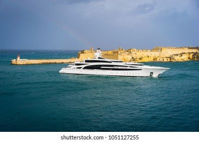 Valletta, Malta - March 7 2017: Luxury yacht entering The Grand Harbour of Malta. Fort Ricasoli with the lighthouse are on the background