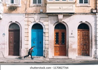 Valletta /Malta - May 1, 2018: A boy running near the doors of Maltese city Valletta