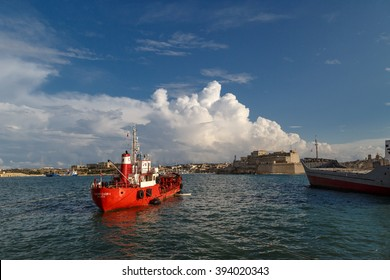 VALLETTA, MALTA - NOVEMBER 2, 2015 : View of Valletta with ships and boats on coastline, on cloudy sky background.