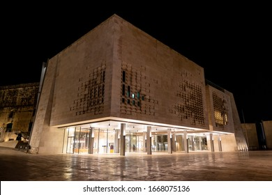 VALLETTA, MALTA - OCTOBER 29, 2019: The modern contemporary building of the Maltese Parliament House (Dar il-Parlament) at night with lights on empty streets