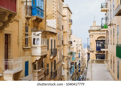Valletta, Malta. Old Town street with traditional maltese balconies and sea view, City of Valletta