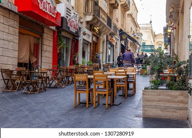 Valletta, Malta, on January 8, 2019. People go along the busy shopping street in the old city. Tables of street cafe wait for visitors