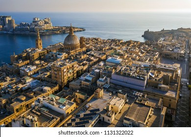 Valletta, Malta - Our Lady of Mount Carmel church and St.Paul's Cathedral from above with Sliema at background at sunrise