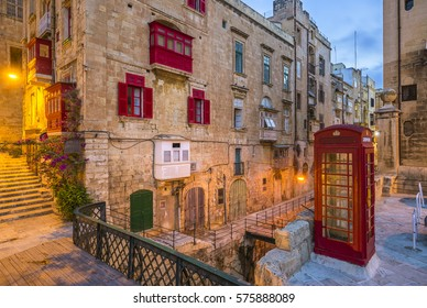 Valletta, Malta - Red vintage british telephone box and footbridge and traditional red balconies in the ancient city of Valletta early in the morning