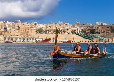 VALLETTA, MALTA - SEP 21, 2016: Tourists cruise in a traditional Maltese dghajsa boat