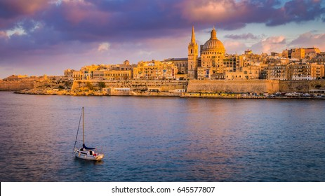 Valletta, Malta - St.Paul's Cathedral in golden hour at Malta's capital city Valletta with sailboat and beautiful colorful sky and clouds