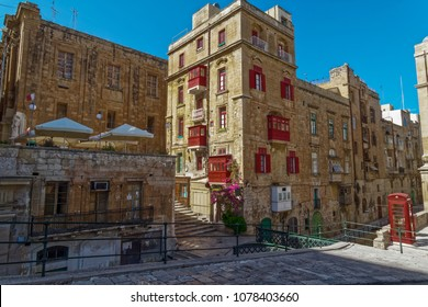 Valletta, Malta Traditional buildings with red balconies. Day view of Maltese limestone buildings with British phone booth in the streets of the capital of Malta.