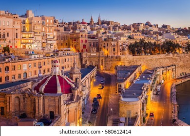 Valletta, Malta - The traditional houses and walls of Valletta, the capital city of Malta on an early summer morning before sunrise with clear blue sky