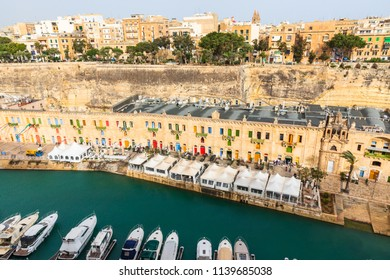 VALLETTA ,MALTA-APRIL 11,2018 :shopping street at the marina is a traditional brown home. Bright doors and windows.The opposite is Yacht port in Valletta the capital of Malta in the morning
