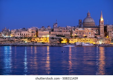 The Valletta skyline with Basilica of Our Lady of Mount Carmel as seen from Sliema at night. Malta