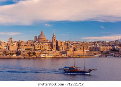 Valletta Skyline with ship at beautiful sunset from Sliema with churches of Our Lady of Mount Carmel and St. Paul's Anglican Pro-Cathedral, Valletta, Capital city of Malta