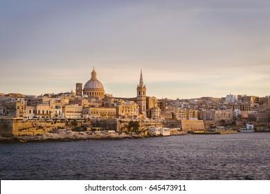 Valletta skyline at sunset with Basilica, viewed from Sliema, Malta