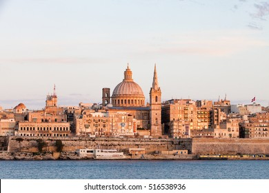 Valletta skyline at sunset with the Carmelite Church dome and St. Pauls Anglican Cathedral, Valletta, Malta