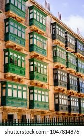 Valletta. Traditional wooden balconies of residential building. Green palette. Malta