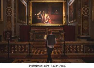 VALLETTA/MALTA - November 17, 2017: Tourist looking at the Caravaggio painting in the Oratory of St. John's Co-Cathedral at Valletta, Malta