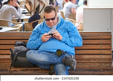 VALLETTA/MALTA - November 23, 2017: Very fat man sitting on the bench and playing with his mobile phone