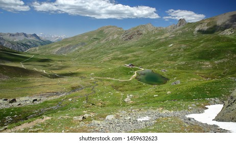 The valley Aigle Blanche (Saint Veran) viewed from the path leading to Blanchet pass, with a lake and Refuge de la Blanche in the foreground, Queyras Regional Natural Park, Southern Alps, France