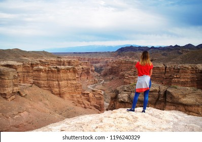 Valley of castles in Yellow Canyon Charyn. National park in East Kazakhstan Almaty region. Dirt road in Canyon. A beautiful tourist girl looks at the Charyn canyon in Kazakhstan.