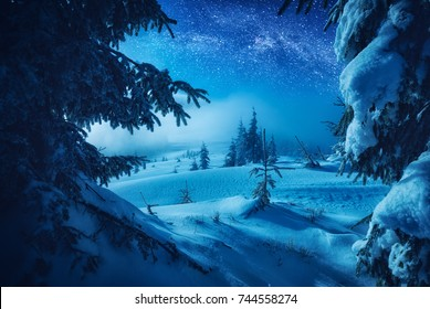 The valley covered with fresh snow in a light of moon. Milky way in a starry sky. Christmas and New Year winter night.