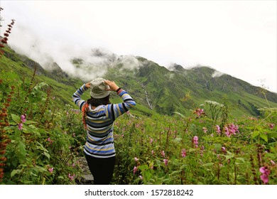 Valley of flowers in September,India,Young female climber walking down grassy rocky hill in green beautiful mountains in india. Woman tourist breathtaking view amazing nature healthy lifestyle,valley