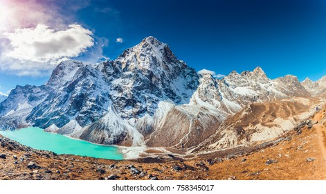 Valley of Himalayan mountains with mountain lake on track to Everest base camp. High mountains with snow-capped peaks. Khumbu valley, Sagarmatha national park, Nepal. Beautiful mountain landscape.