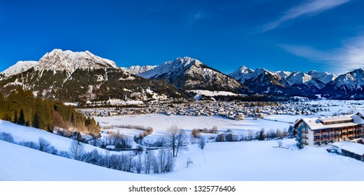 The valley Kleinwalsertal and Oberstdorf, Germany, with Alps in the winter with snow covered landscape in the afternoon.