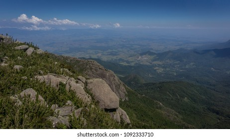 Valley landscape with blue sky, clouds and green nature, seen from the top of a mountain in Brazil