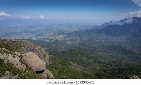 Valley landscape with blue sky and green nature, seen from the top of a mountain in Brazil.