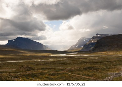 Valley with mountains in the distance and water flowing through a river during the hike of Kungsleden (Kings path) in northern Sweden.