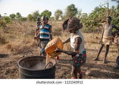 VALLEY OMO, ETHIOPIA - MARCH 12 2012: Unidentified Hamer man prepares sorghum beer at festival dedicated to initiation for young men, Dimeka, Ethiopia. Homemade beer is popular with local tribes.