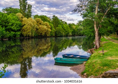 Valley of the river Dordogne two boats moored in the calm waters of the Dordogne in its passage through the village of Carennac France