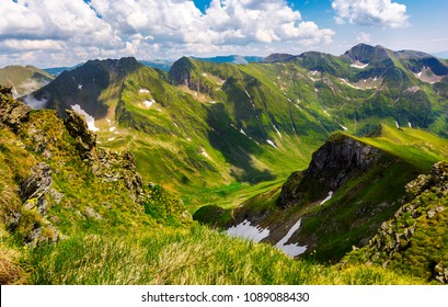 valley with snow in summer mountains. gorgeous mountainous landscape of Carpathians. rocky cliffs and grassy hillsides under a cloudy sky. Fagaras ridge of Southern Carpathian mountains, Romania
