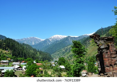 Valley surrounded by snow mountains and mountains with trees with clear blue sky