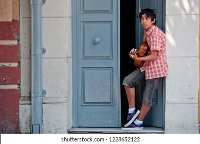 Valparaiso / Chile - Feb 2012: The young latin boy plays the guitar near the door in the historic city of Valparaiso, UNESCO World Heritage.