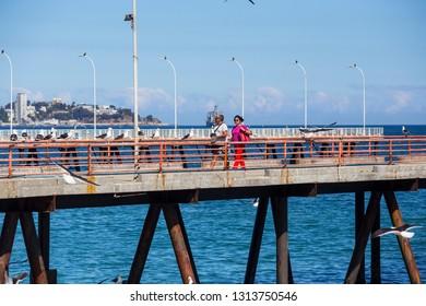 VALPARAISO, CHILE - February 2019: People walking on the pier near fish market in Valparaiso, Chile