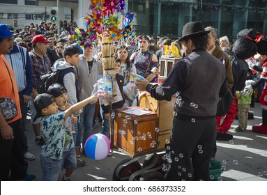 """Valparaiso, Chile. May 21, 2017. Civic military celebration for May 21 in the port of Valparaiso. """"Organillero"""" Organ grinder, traditional character with its parrot and its products for children."""
