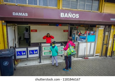VALPARAISO, CHILE - SEPTEMBER, 15, 2018: Outdoor view of unidentified woman with her daugher at the enter of public bathrooms on Valparaiso, surrounding of old buildings