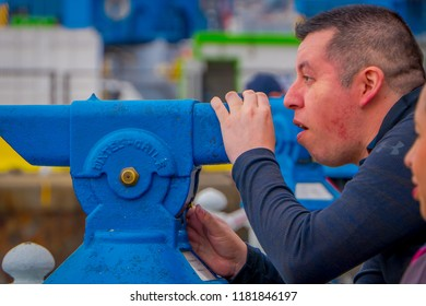 VALPARAISO, CHILE - SEPTEMBER, 15, 2018: Uindentified man using a coin binocular machine located in the Port of Valparaiso, it is an important port city on the Pacific Coast of Chile