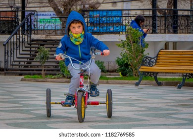 VALPARAISO, CHILE - SEPTEMBER, 15, 2018: Outdoor view of unidentified little boy wearing blue jacket for cold weather and riding his tricyle in a square of a park located in dowtown on Valparaiso
