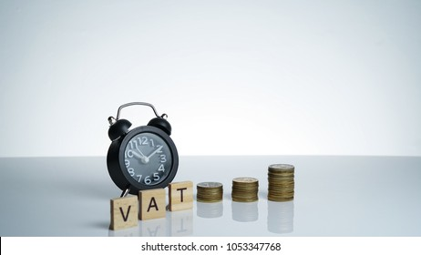 Value Added Tax (VAT) Conceptual image with Black retro alarm clock with coins and wooden text block