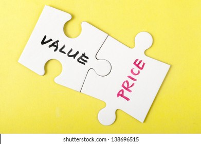 Value and price words written on two pieces of jigsaw puzzle