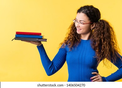 Value and weight of knowledge. Self motivation, education and improvement. Smart lady holding set of notebooks. Copy space.