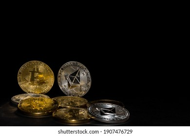 valueable golden bitcoin and silver ether coins from cryptocurrency on black background
