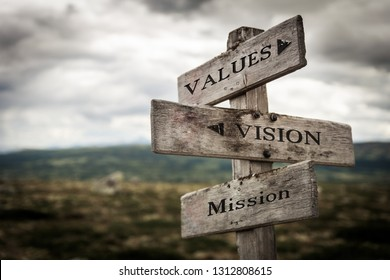 Values, vision, mission vintage wooden signpost in nature. Moody, signpost, board, quote, message, business, corporate concept.
