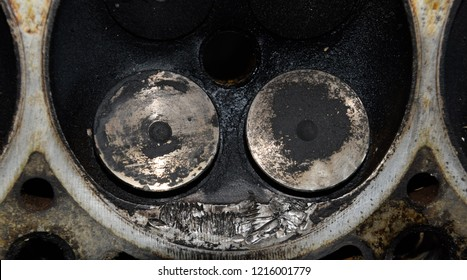 Valve in a deposit on the removed cover of the engine valve box. Engine repair. Imprint of the thread of the bolt that fell into the engine cylinder.
