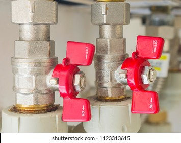 Valves for flow control of cold and hot water in the heating boiler. Close up, selective focus.