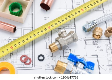 Valves, pipe fittings, and tape measure on a building plan background