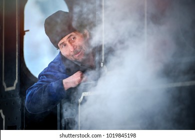Vama, Romania-27 January 2018: Steam train conductor that stands on the train with the steam from the locomotive that comes in front of it