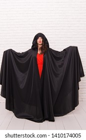 Vampire in cloak sexy devil girl. Woman tempting vampire demon. Girl covered with cloak. Devil concept. Halloween masquerade. Halloween party. Damn pretty woman devil. Death in black cloak symbol.