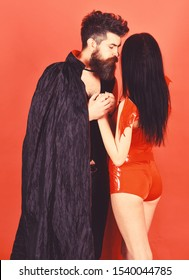 Vampire in cloak and sexy devil girl holds hands. Couple in love, perfect match. Couple on pensive faces play role game. Man and woman dressed like vampire, demon, red background. Halloween concept.